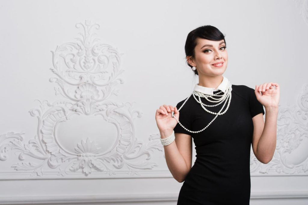 Woman playfully wearing little black dress adorned with pearls