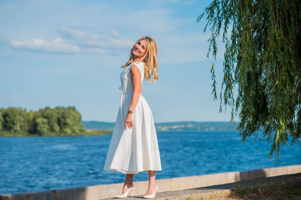 Woman wearing white midi dress with white heels for a timeless and airy look